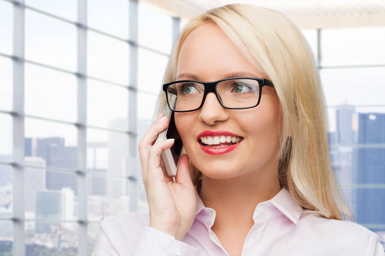 blonde woman wearing glasses and talking on the phone