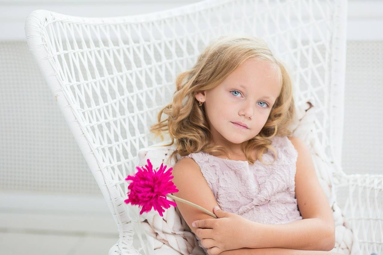 young blonde girl sitting in white chair with pink flower