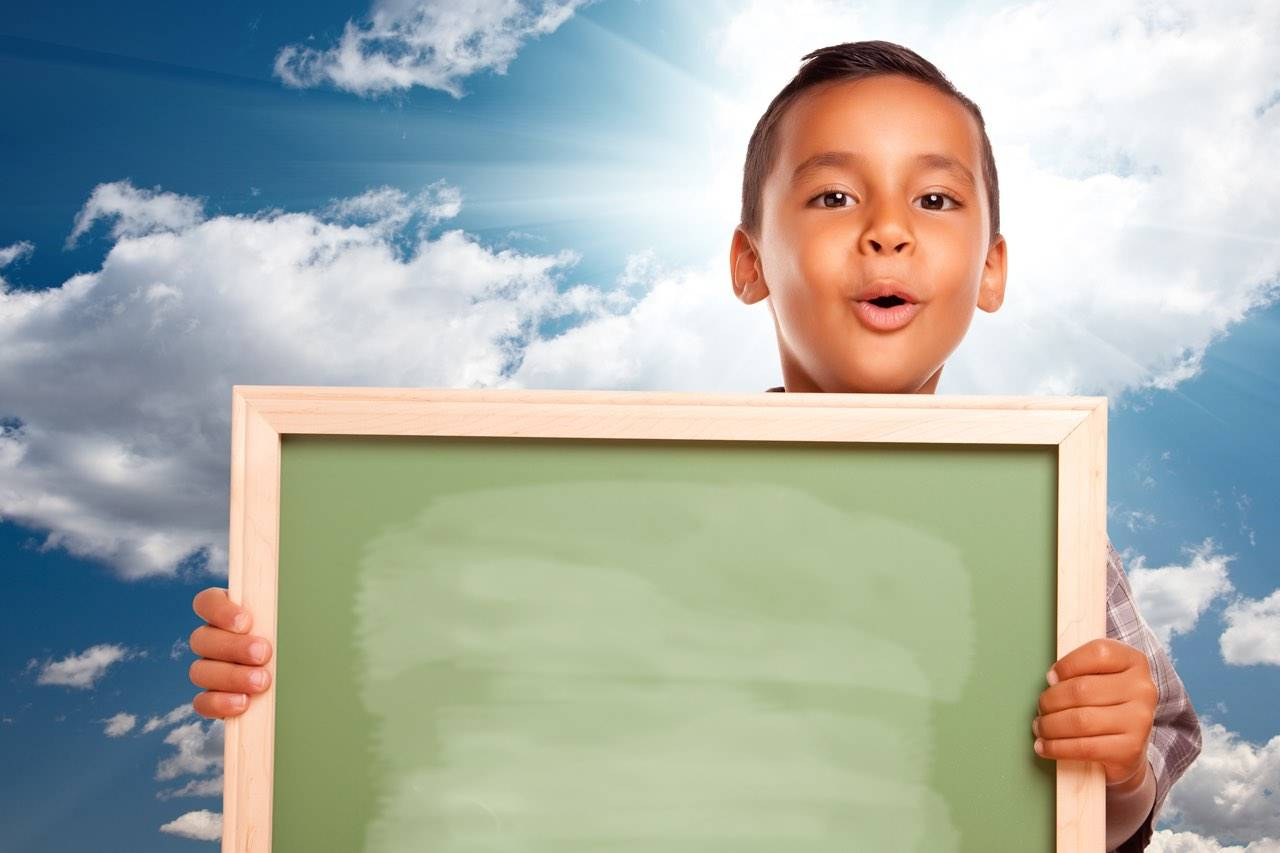 school boy holding chalkboard