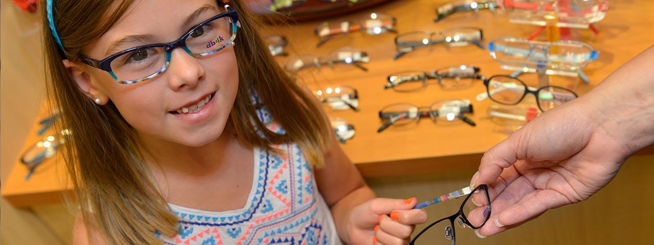 little girl trying on glasses 1280x480