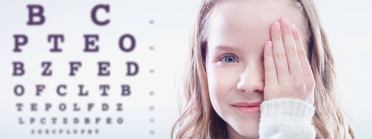 close up of young blonde girl covering one eye in front of eye chart